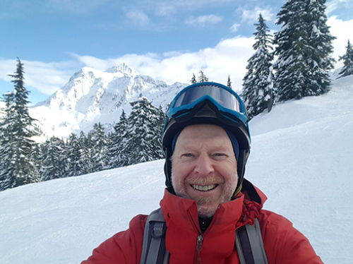 dan jaffe on ski slopes with Mt. Rainier in the background